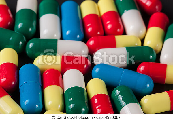colorful pills on a dark background - csp44930087