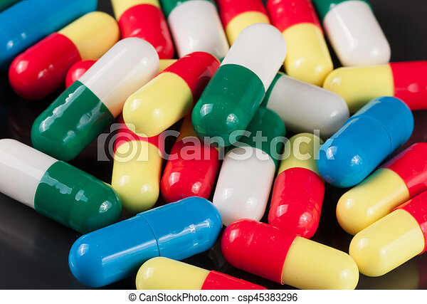 colorful pills on a dark background - csp45383296