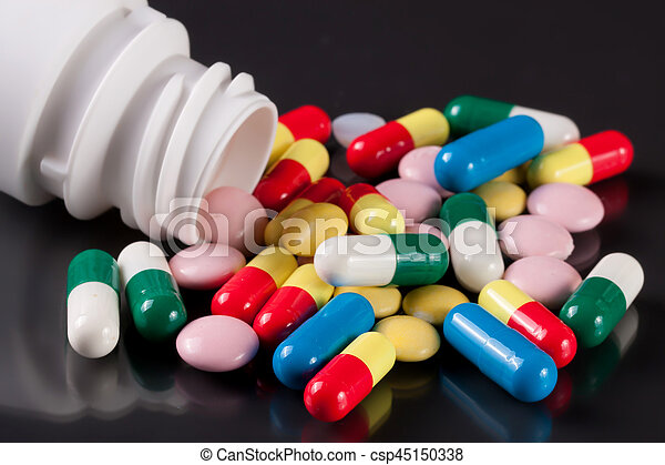 colorful pills on a dark background - csp45150338