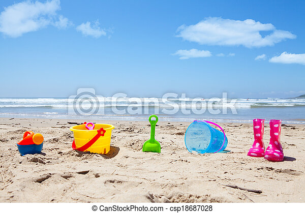 Colorful plastic toys and gumboots on beach sand - csp18687028