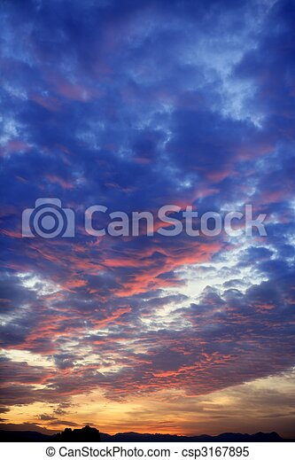 Colorful red blue sunset cloudy sky - csp3167895