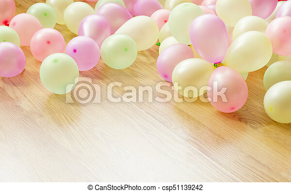 Colorful small balloons lying on wooden floor - csp51139242