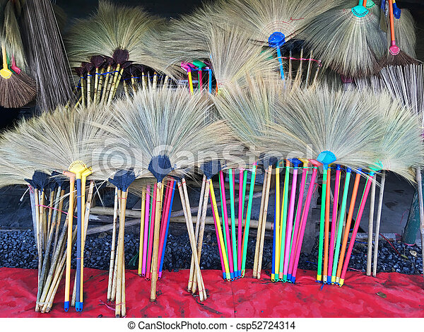 colorful straw brooms at grocery store - csp52724314