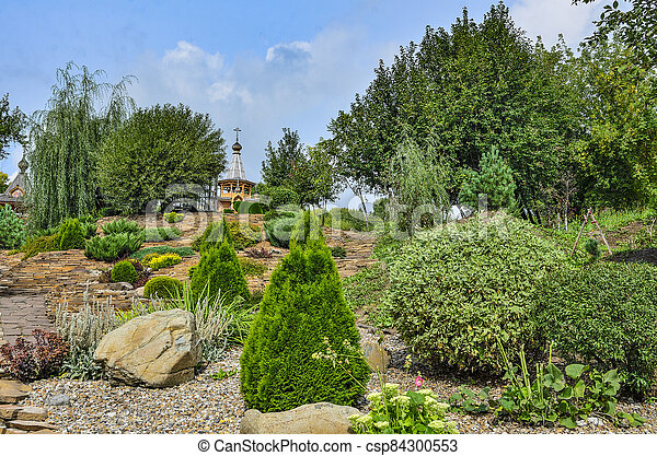 Colorful summer rockery garden at bright sunny day - csp84300553