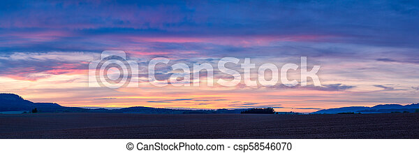 Colorful sunset over plowed fields in Northern Bohemia in the Czech Republic - csp58546070