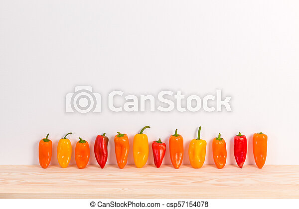 Colorful sweet peppers on wooden surface - csp57154078