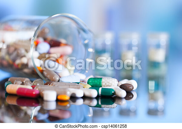 Colorful tablets with capsules and pills on blue background - csp14061258