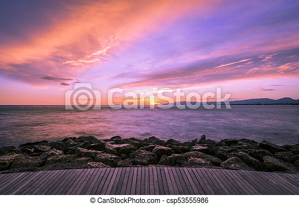 Colorful ultra violet dark sunset over the sea and with a wooden walkway and rocks on the foreground. - csp53555986