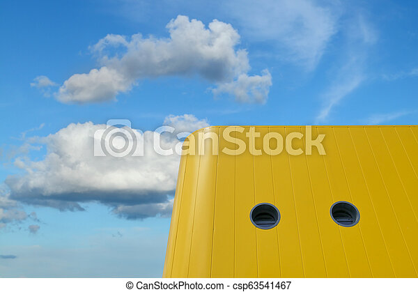 Colorful yellow modern building and blue sky with clouds - csp63541467