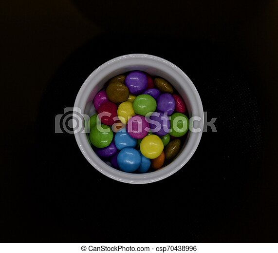 Coloured sweets in white pot against black background - csp70438996