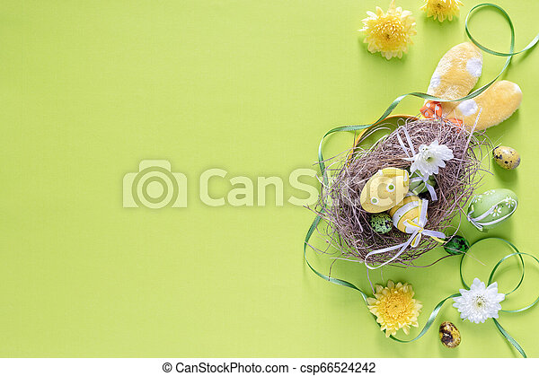 Colourful Easter eggs in birds nest with festive decoration on green background, top view- image - csp66524242