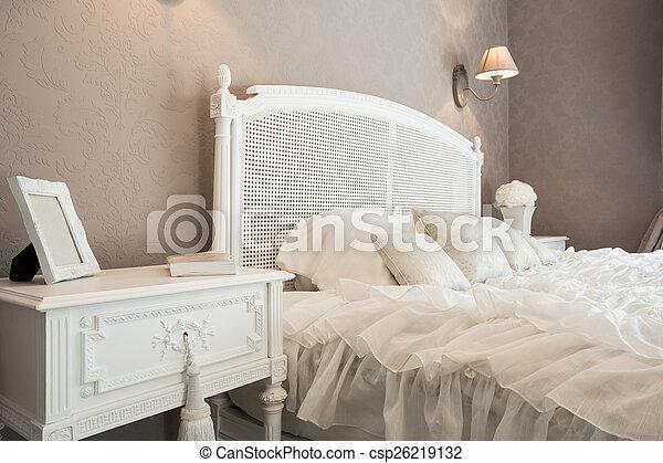 Comfortable bed in a bedroom - csp26219132