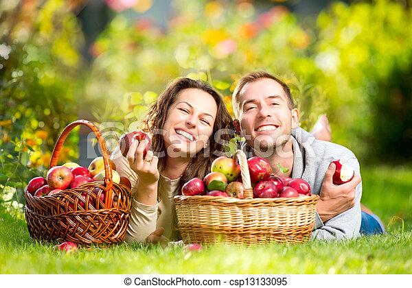 Una pareja descansando en la hierba y comiendo manzanas en el jardín de otoño - csp13133095