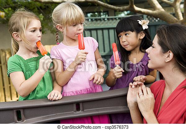Niños de preescolar en el patio con maestros comiendo helados - csp3576373