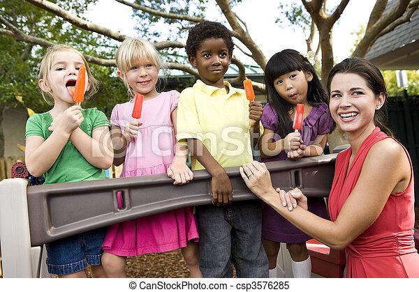 Niños de preescolar en el patio con maestros comiendo helados - csp3576285