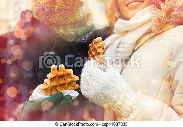 Cerca de una pareja feliz comiendo gofres al aire libre - csp41037333