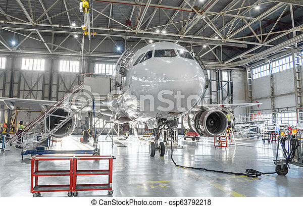 Commercial aircraft jet on maintenance of engine and fuselage check repair in airport hangar. - csp63792218