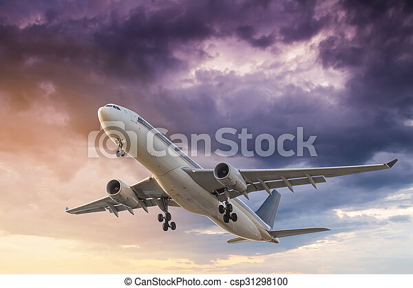 Commercial Airplane Flying At Sunset With Storm Clouds Background