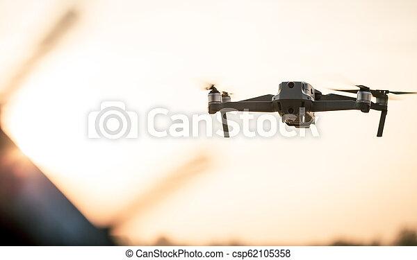 Drone como Mavic 2 Pro volando durante el atardecer. - csp62105358