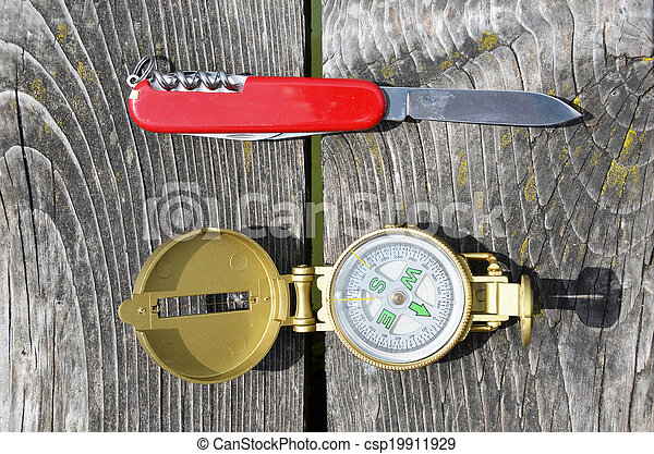 Compass and pocket knife on the wooden background  - csp19911929