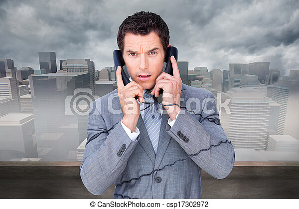 Composite image of angry businessman tangle up in phone wires - csp17302972