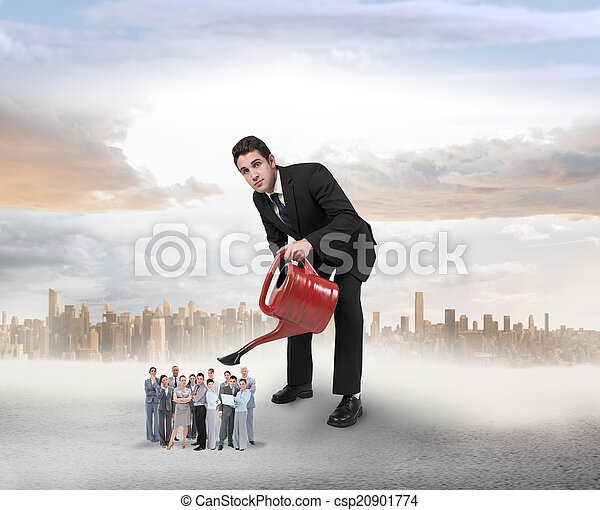 Composite image of businessman watering tiny business team - csp20901774