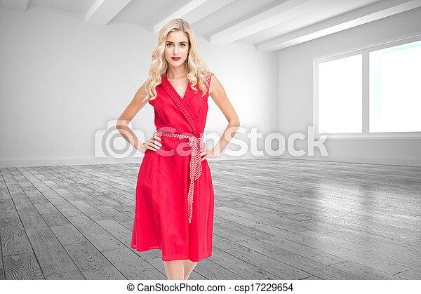 Composite image of elegant blonde standing hands on hips - csp17229654