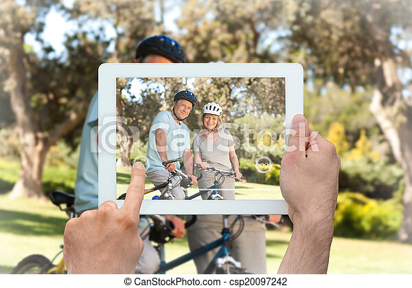 Composite image of hand holding tablet pc - csp20097242
