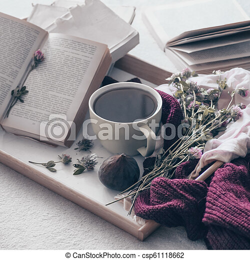Composition of a cup of tea and opened book is not readable on a coffee table in the room, with figs and flowers. close up - csp61118662