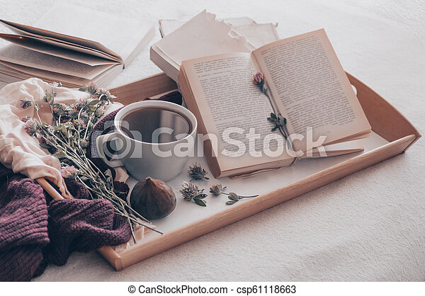 Composition of a cup of tea and opened book is not readable on a coffee table in the room, with figs and flowers. close up - csp61118663