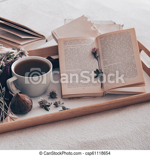 Composition of a cup of tea and opened book is not readable on a coffee table in the room, with figs and flowers. close up - csp61118654