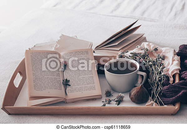 Composition of a cup of tea and opened book is not readable on a coffee table in the room, with figs and flowers. close up - csp61118659