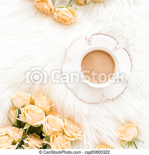 Composition of pastel tea rose bouquet flowers and a Cup of cocoa on white background. Floral background. Flat lay, top view. - csp83800322