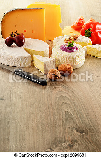 Composition with different sorts of cheese on wooden table - csp12099681