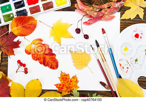 Composition with sheet of white paper, paints, brushes and autumn colorful leaves. - csp40764100