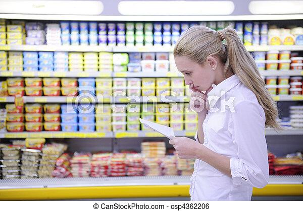 Una mujer leyendo su lista de compras en el supermercado - csp4362206