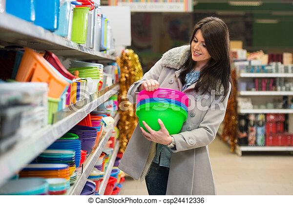 Una mujer joven comprando en el supermercado - csp24412336