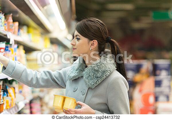 Una mujer joven comprando en el supermercado - csp24413732