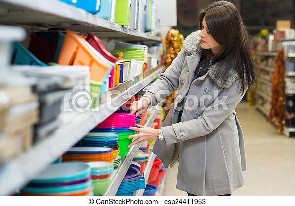 Una mujer joven comprando en el supermercado - csp24411953