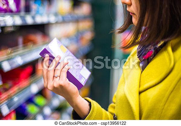 Una joven comprando en el supermercado - csp13956122
