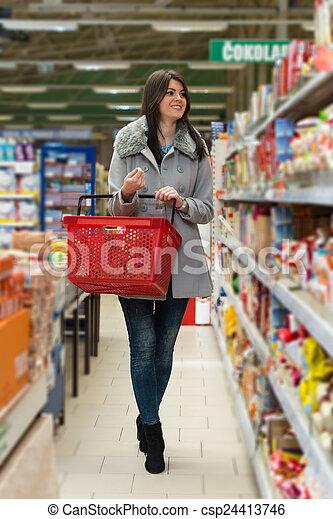 Una mujer joven comprando en el supermercado - csp24413746