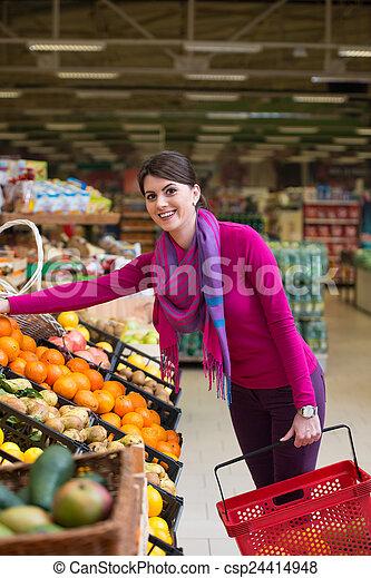 Una mujer joven comprando en el supermercado - csp24414948