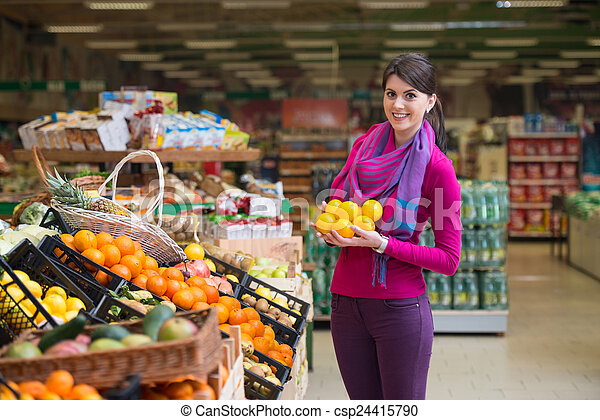 Una mujer joven comprando en el supermercado - csp24415790