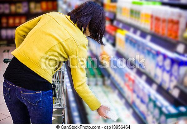 Una joven comprando en el supermercado - csp13956464