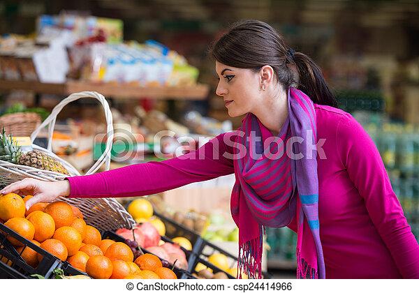 Una mujer joven comprando en el supermercado - csp24414966