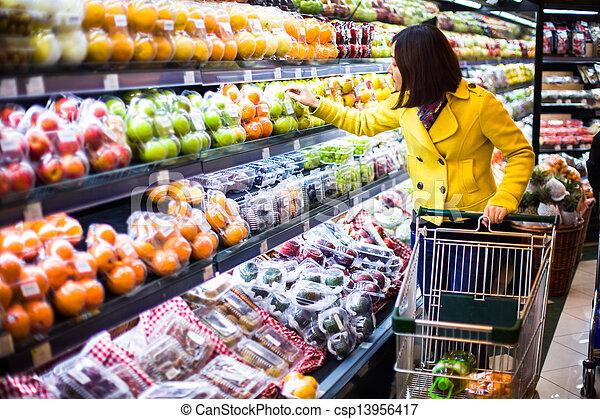 Una mujer joven comprando en el supermercado - csp13956417