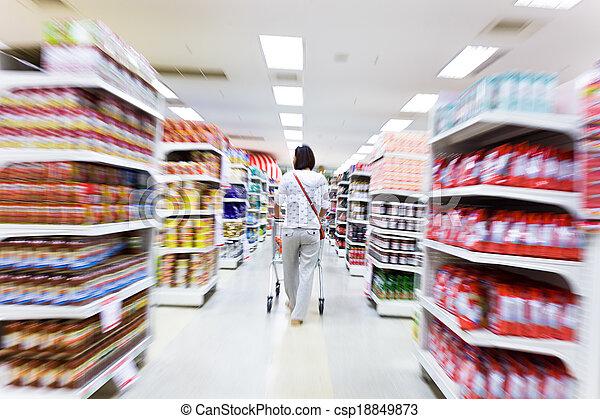 Una mujer joven comprando en el supermercado - csp18849873