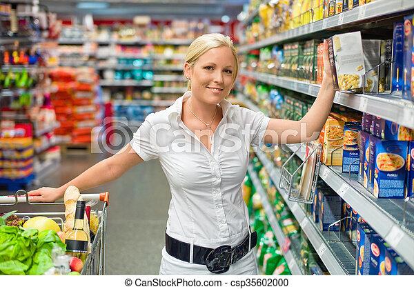 Una mujer con un carrito en el supermercado - csp35602000