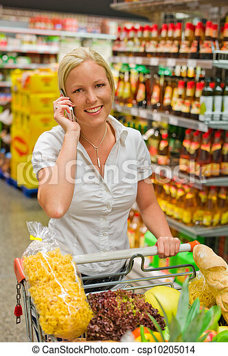 Una mujer con un carrito en el supermercado - csp10205014