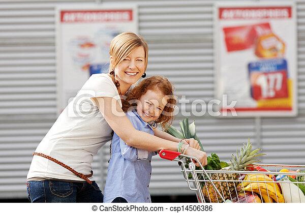 Chica y madre empujando carritos de compras al aire libre - csp14506386